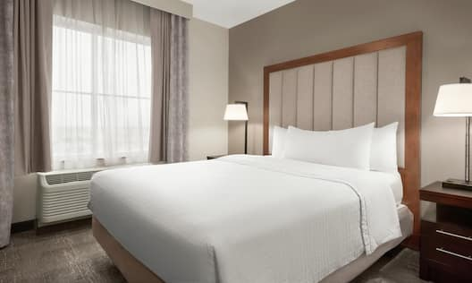 Bright bedroom in suite featuring comfortable queen bed, bedside tables with lamps, and air conditioning unit by window.