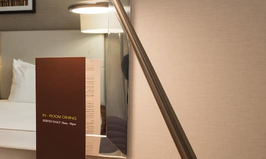 "Reflection of Wall Art and Bed in Mirror Above Desk With  Illuminated Lamp by ""In-Room Dining"" Sign"