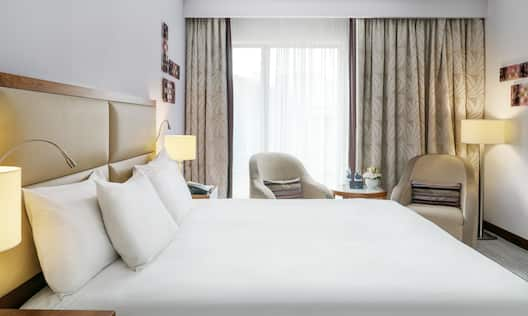Deluxe Room Bed and Window
