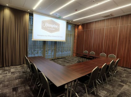 Chairs and U-Shaped Table with Projector Screen in Conference Room