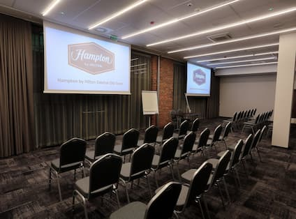 Conference Room with Tables, Projector Screens, and Easel