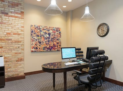 Business Center With Printer/Fax/Copier, Wall Art, Wall Clock, Two Computer on Desk, and Two Chairs