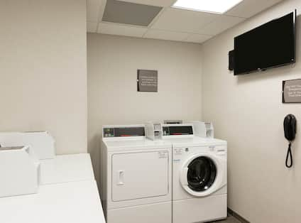 Coin Operated Washing and Drying Machines, TV, Signage, and Phone in Guest Laundry Area
