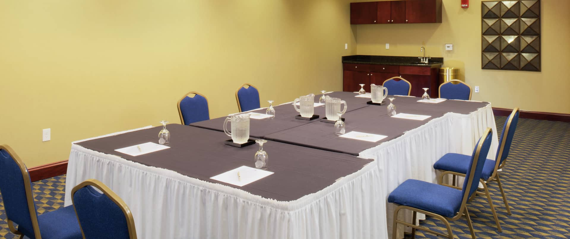 Water Pitchers, Drinking Glasses, Note Pads, and Blue Chairs at Tables in Meeting Space