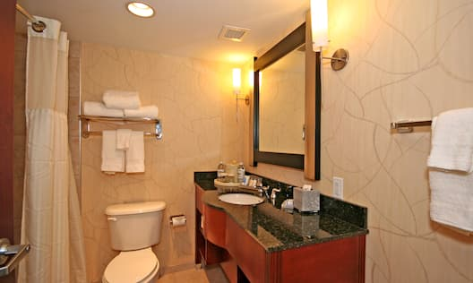 Open Door To View of Bathtub, Fresh Towels on Racks Above Toilet, Vanity Mirror, Sink, Toiletries, and Amenities in Guest Bathroom
