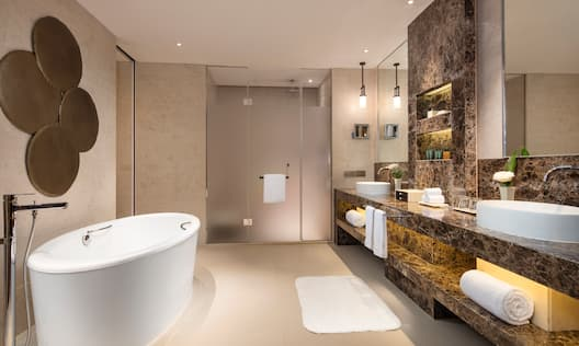 Ocean Suite Bathroom with Sink/Vanity Under Mirror, Shower with Glass Doors, and Freestanding Tub Towels, and Toiletries
