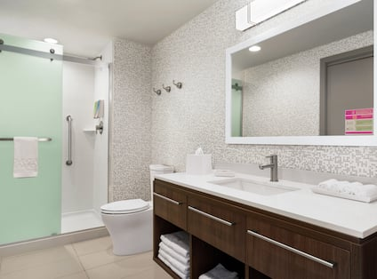 Spacious guest bathroom featuring stand up shower with frosted glass doors, vanity, and mirror.