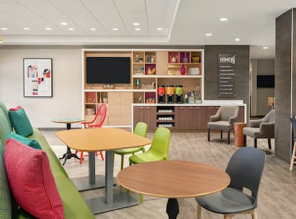 Bright lobby area featuring comfortable seating, TV, and coffee bar.
