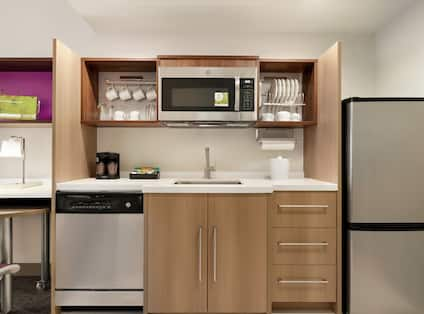 Bright studio suite work desk and kitchen fully equipped fridge, dishwasher, microwave, and coffee maker.
