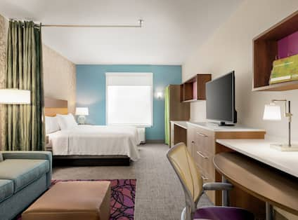 Bright studio suite featuring pull out sofa bed, work desk, TV, comfortable king bed, and air conditioning unit by window.