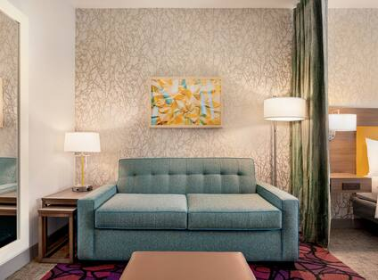 Studio suite lounge area featuring pull out sofa bed, ottoman, mirror, and textural patterned wall.