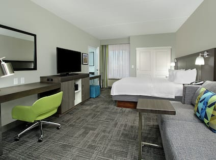 King Bed, TV, Work Desk, and Lounge Area in Whirlpool Suite