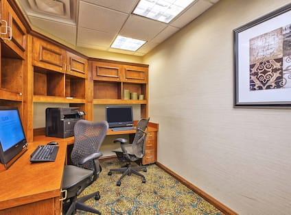 Business Center With Two Computer Workstations, Rolling Chairs, Printer/Fax./Copier, and Wall Art
