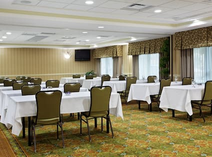 Classroom Style Meeting Room With Tables, Seating for 24, and TV in Corner by Windows