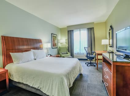 One King Bed Guest Bedroom with HDTV, Work Desk and Armchair