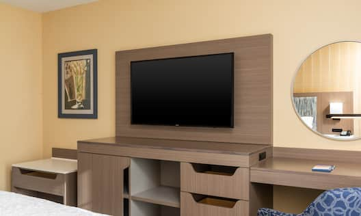 TV in room with workdesk and mirror