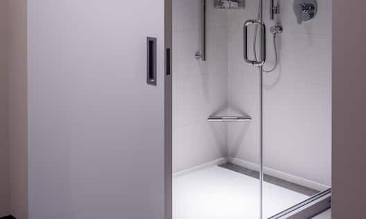 Shower with Glass Doors and Handheld Showerhead Behind Open Sliding door