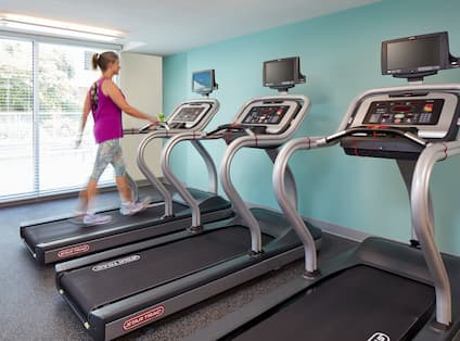 Woman on One of Three Fitness Center Treadmill by Large Windows