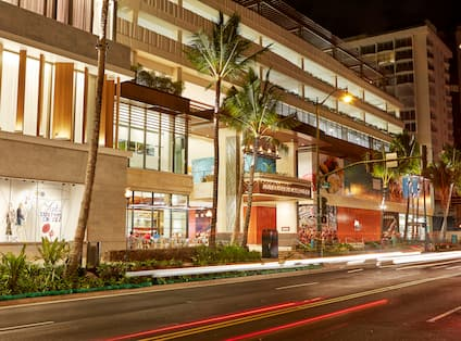 Street View of Illuminated Hotel Entrance and Landscaping at Night
