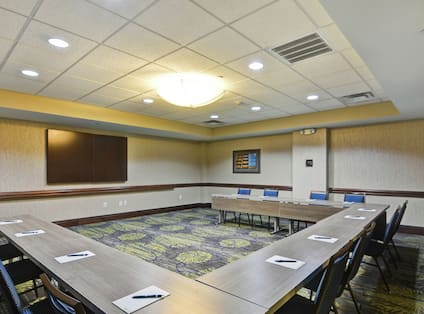 Sage Meeting Room With U-Shaped Table, Chairs, and TV