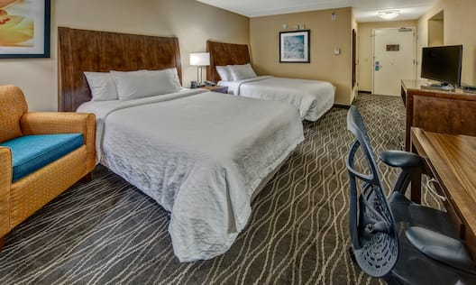 Accessible Room With Wall Art, Reading Chair in Corner, Two Queen Beds, Bedside Table With Lamp, View of Entry, TV, and Work Desk