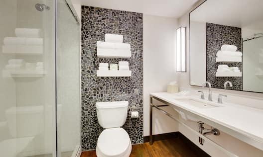 Standard Bathroom Shower With Glass Doors, Fresh Towels Above Toilet, Brightly Lit Vanity Mirror, Sink, and Amenities