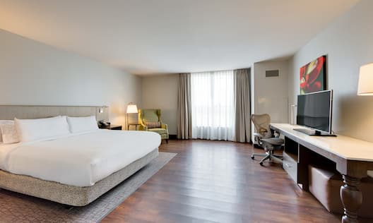 Accessible Guest Room With King Bed, Bedside Tables With Reading Lamps, Arm Chair in Corner by Window, Work Desk, Wall Art and TV