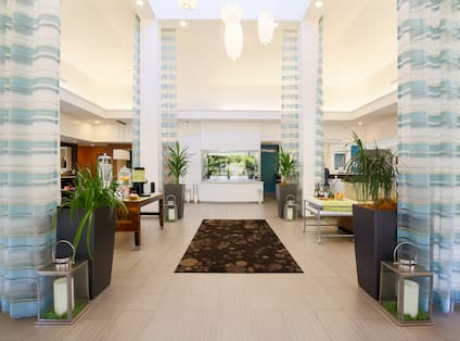 Vast Pavilion Lobby With Long Drapes, Decorative Lighting, Two Beverage Stations, Lounge Seating and View of Front Desk