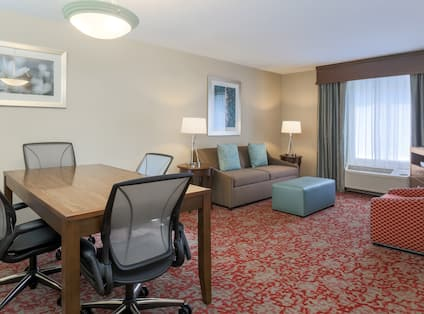 Boardroom Table With Seating for Four, and Living Area With Sofa, Lamps, Ottoman, TV, and Arm Chair