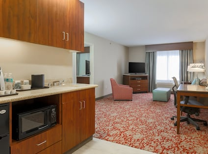Suite Dinette Area With Mini Fridge, Microwave, Keurig, and View of Living Area Arm Chair, TV by Window, Sofa, and Work Desk