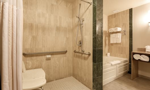 Roll-in Shower With Bench, Grab Bars, Handheld Showerhead, Tub With Fresh Towels, and Illuminated Vanity area
