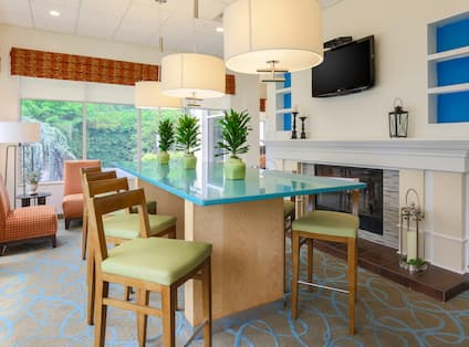 Chairs in Corner by Windows, High Table Seating, and TV Above Fireplace in Lobby Area