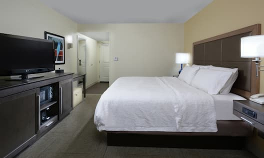 King-Sized Bed Facing TV in Guest Room