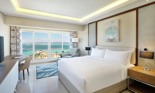 Hotel Guest Room with One Queen Bed and Wall of Windows Overlooking the Sea