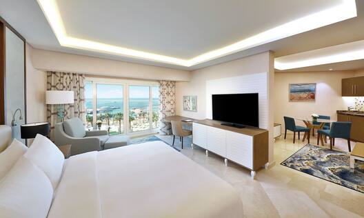 King Family Junior Suite with Bed and Lounging Area with View of the Sea and Space is Open to the Kitchen and Dining Area