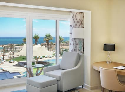 Hotel Guest Suite with Chair Positioned by Wall of Windows and a Breathtaking View of the Beach and the Red Sea