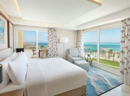 Hotel One King Guest Room Suite with Wall of Windows Overlooking the Beach to the Sea and a Glass Door to Balcony