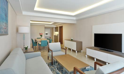 Living Area with Sofa, Coffee Table, Soft Seating Chairs, Cradenza with TV and Dining Table and Kitchen in the Background