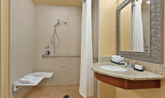 Accessible Guestroom Bathroom with Roll-In Shower and Seat, Mirror, and Vanity