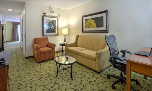 TV, Opening to Bedroom, Arm Chair, Sofa, Wall Art, Glass Table, and Work Desk in Suite Living Area