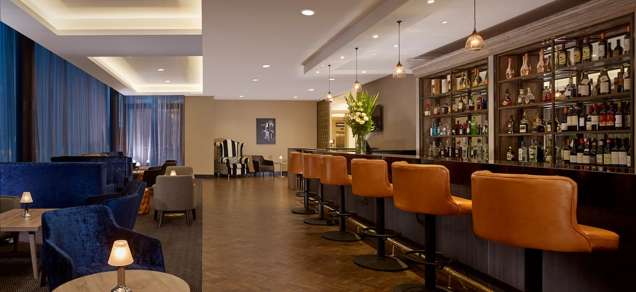 Hotel Lounge with Seating at the Bar and Booths along a Wall of Windows with View of the City