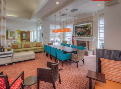 Soft Seating, Wall Art, Table With Seating for 10 by Fireplace in Lobby Lounge Area