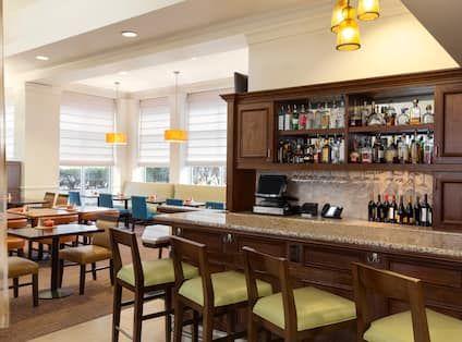 Fully Stocked Bar With Angled Green Bar Chairs and Table Seating by Windows in Background