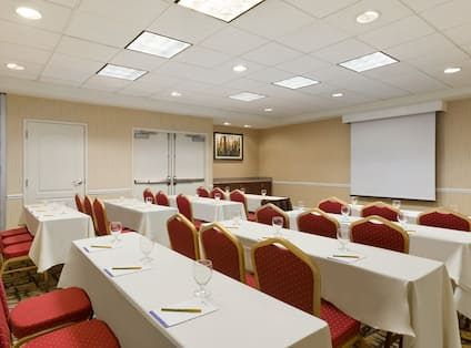 Meeting Room in Classroom Setting With Tables and Chairs Facing Presentation Screen