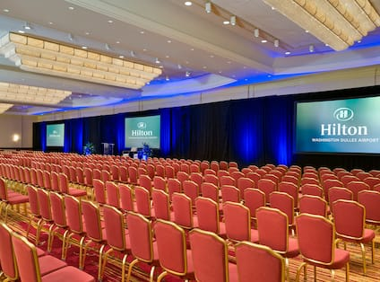 Belmont Theater Arranged Theater Style With Rows of Chairs Facing Two Projector Screens, Two Armchairs, and Podium