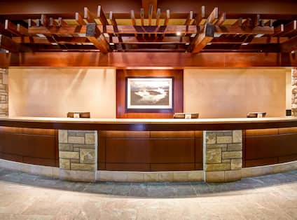 Hotel front desk with art displayed on the wall behind counter