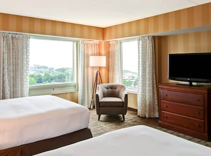 Two queen beds with soft chair, TV, and two corner windows with outdoor view