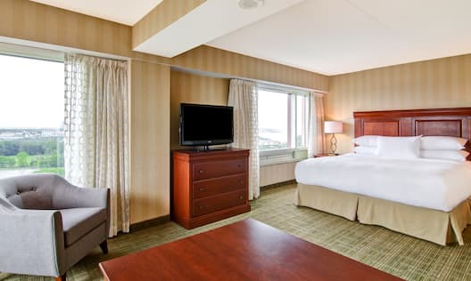 Suite with king bed, work desk, soft chair, TV, and windows with outdoor view
