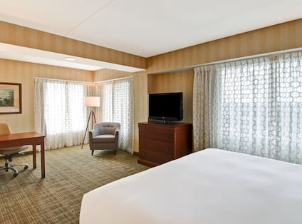 King suite with bed, soft chairs, work desk, TV, and multiple windows with shades drawn