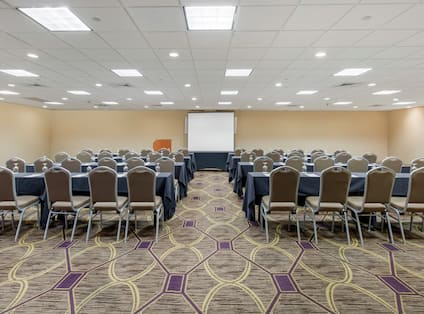 Meeting Room with Projector Screen, Tables, and Chairs